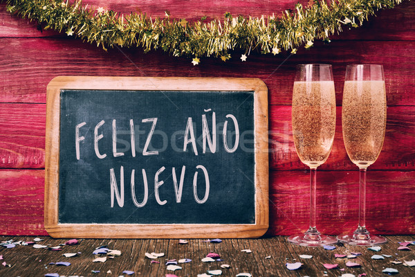 champagne and text feliz ano nuevo, happy new year in spanish Stock photo © nito