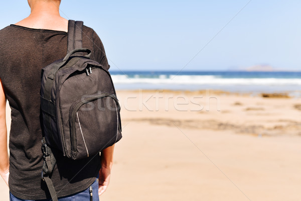 young man with a backpack on the beach Stock photo © nito