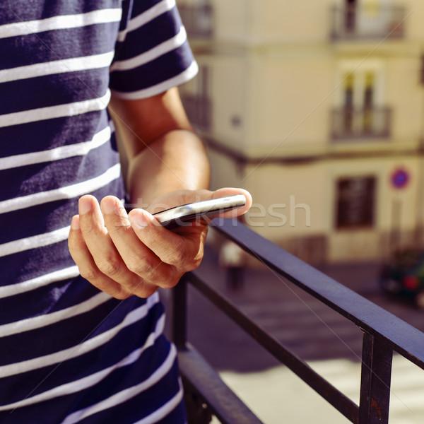 молодым человеком смартфон балкона молодые кавказский Сток-фото © nito