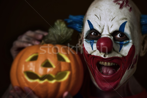 Stock photo: evil clown with a carved pumpkin