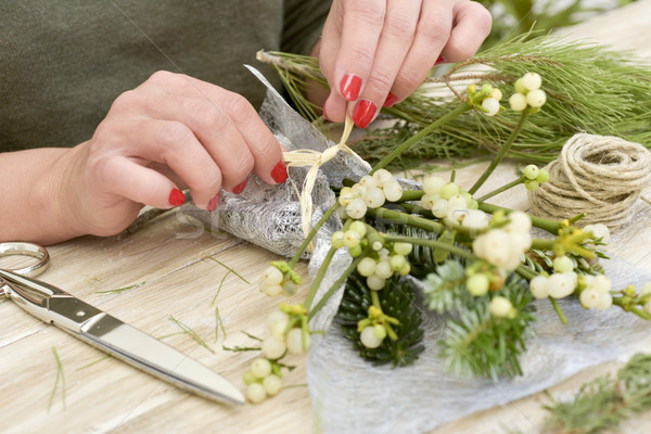 woman arranging a bunch of mistletoe Stock photo © nito