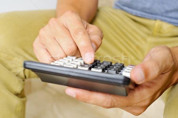 young man using a calculator Stock photo © nito