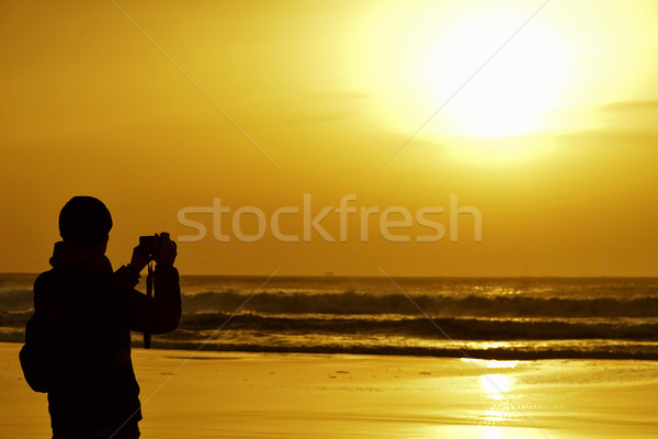 young man taking a picture in front of the sea at dusk Stock photo © nito