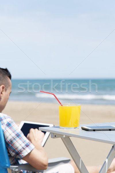 man using a tablet on the beach Stock photo © nito