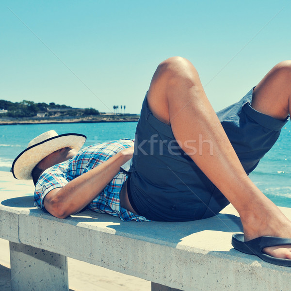 young man lying down in a street bench near the sea Stock photo © nito