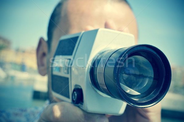 Stock photo: young man filming with a retro film camera