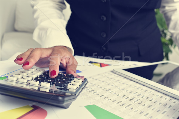 businesswoman using an electronic calculator in her office Stock photo © nito