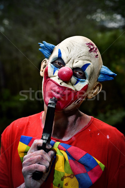 scary evil clown blowing his gun in the woods Stock photo © nito