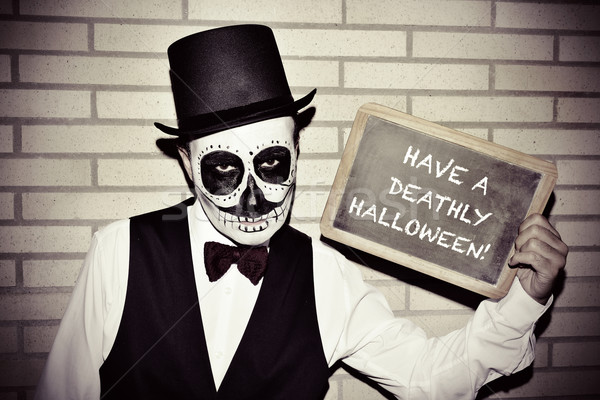 man with calaveras makeup, with chalkboard with text have a deat Stock photo © nito