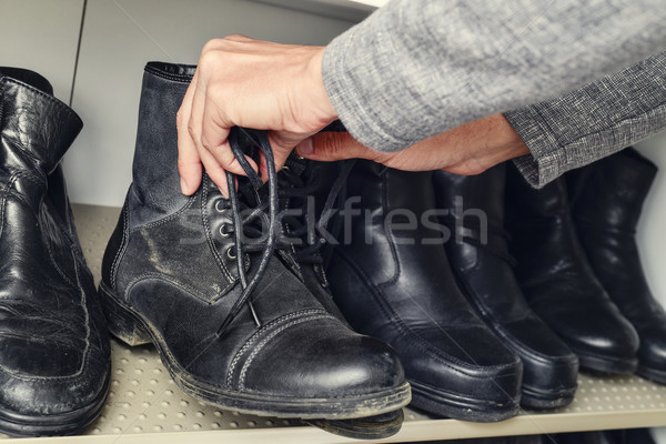 young man picking a pair of boots from the closet Stock photo © nito
