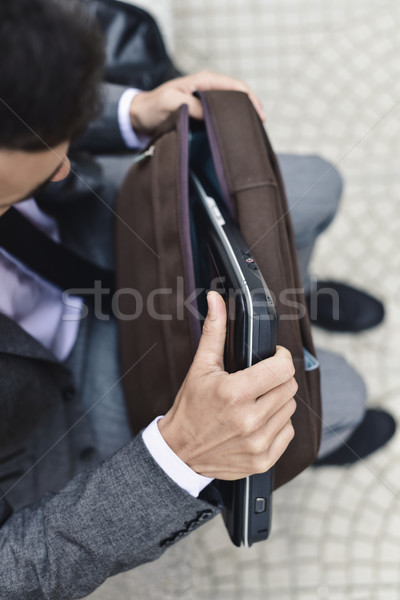 businessman taking a laptop out of a briefcase Stock photo © nito