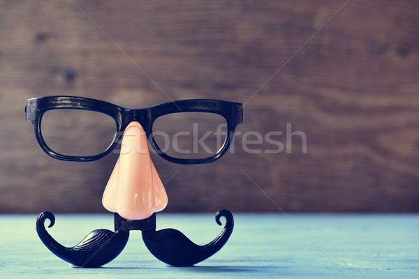 fake mustache, nose and eyeglasses on a blue surface Stock photo © nito