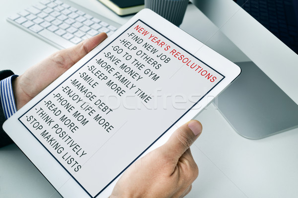man with a list of new years resolutions in a tablet Stock photo © nito