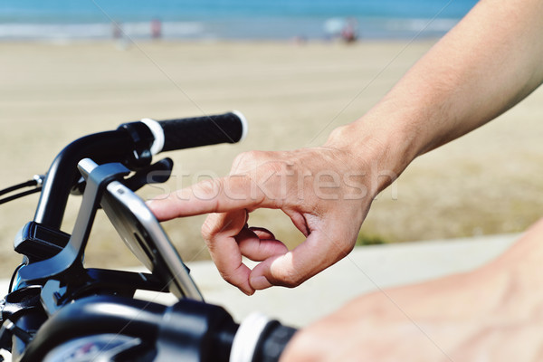 young man using a smartphone riding a bicycle Stock photo © nito