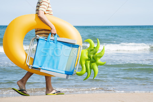 man carrying a swim ring and a beach chair Stock photo © nito