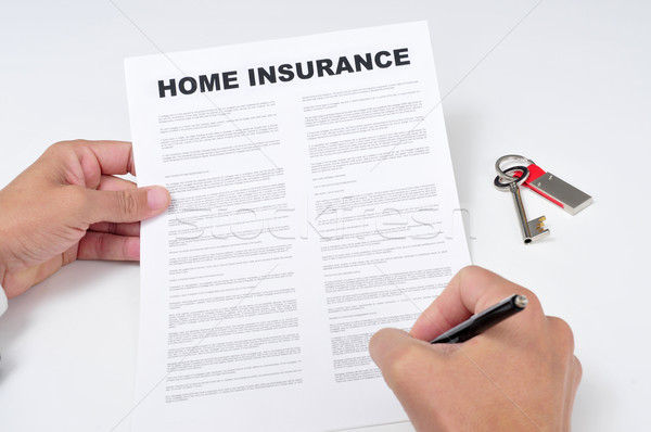 a young man signing a home insurance policy Stock photo © nito