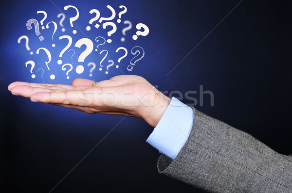 Stock photo: question marks on the hand of a young man