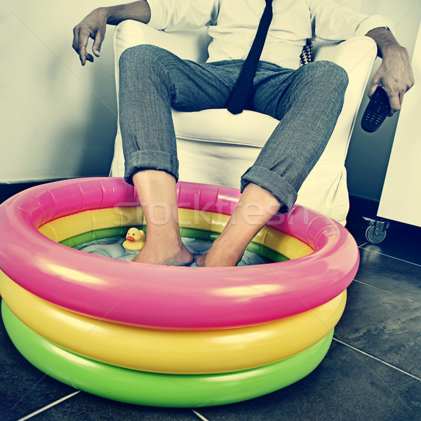 man in suit soaking his feet in an inflatable water pool, with a Stock photo © nito