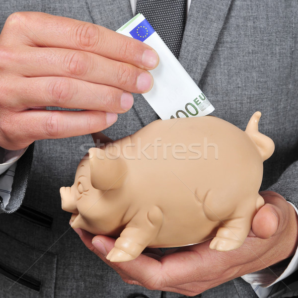 man in suit introducing a euro bill in a piggy bank Stock photo © nito