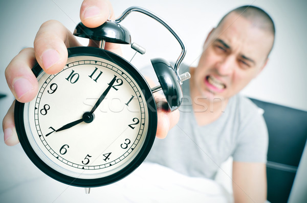 angry young man in bed holds his alarm clock Stock photo © nito