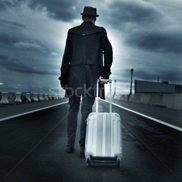 young man with a rolling suitcase, with a dramatic effect Stock photo © nito