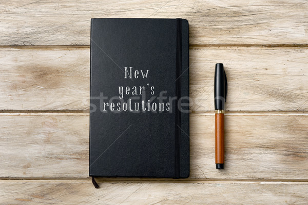 Stock photo: text new years resolutions in a notebook