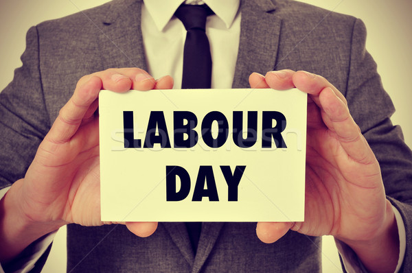 man showing a signboard with the text labour day, filtered Stock photo © nito