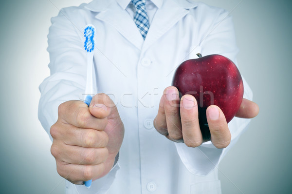 a dentist showing a toothbrush and an apple Stock photo © nito
