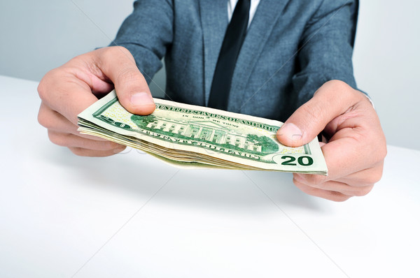 man in suit with a wad of american dollar bills Stock photo © nito