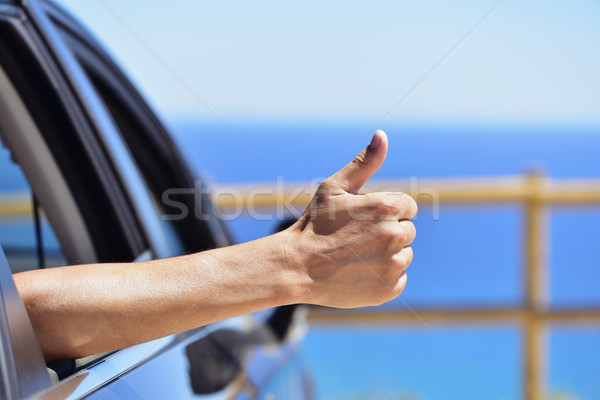 man giving a thumbs up sign in a car near the ocean Stock photo © nito