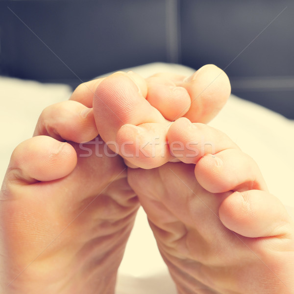 young man rubbing his bare feet together in bed Stock photo © nito