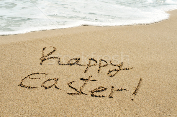 happy easter written in the sand of a beach Stock photo © nito