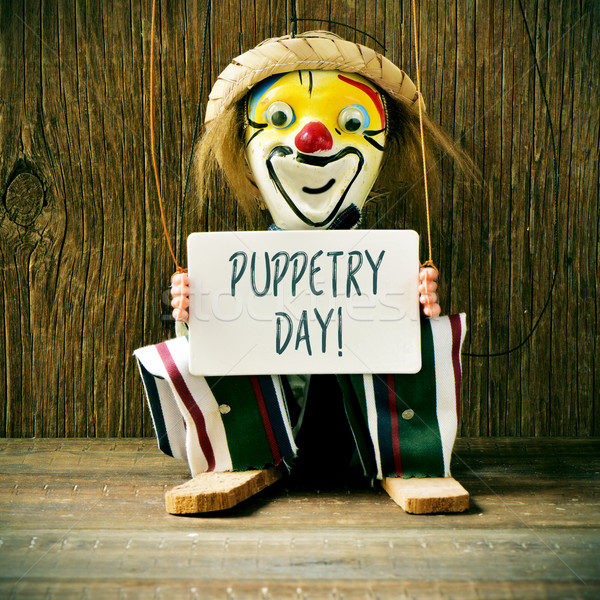 Stock photo: old marionette with a signboard with the text puppetry day