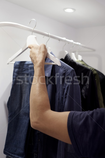 young man hanging or unhanging a pair of jeans Stock photo © nito