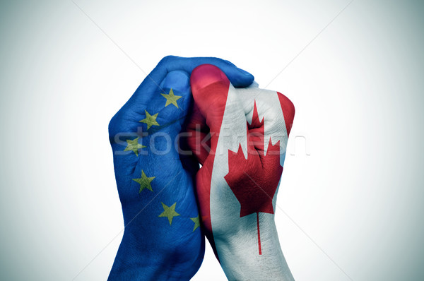 hands patterned with the European and the Canada flags put toget Stock photo © nito