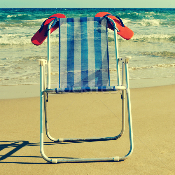 deckchair and orange flip-flops on the beach, with a retro effec Stock photo © nito