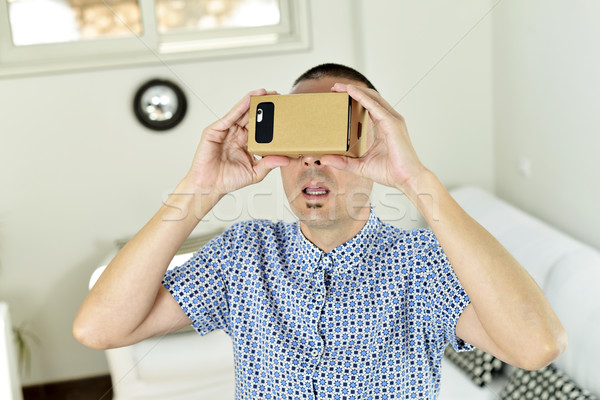 young man with cardboard virtual reality lenses Stock photo © nito