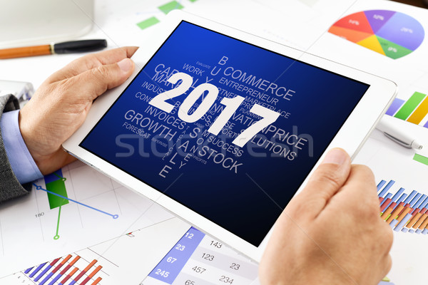 Stock photo: man with tag cloud of goals for 2017 in tablet