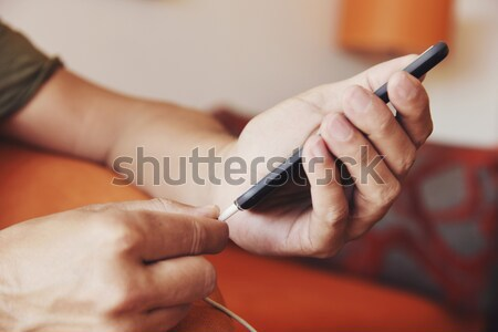 man plugging a cable to his smpartphone Stock photo © nito