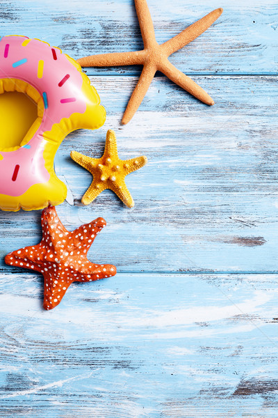 inflatable donut and starfishes on a blue wooden surface Stock photo © nito