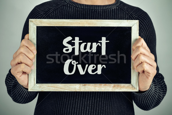 man with chalkboard with the text start over Stock photo © nito