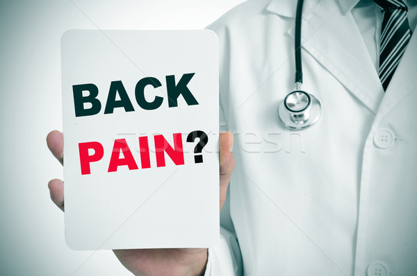 doctor with a signboard with the question back pain? Stock photo © nito