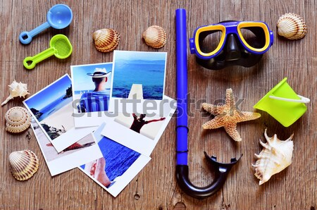 retro camera, starfish and some photos on a wooden surface Stock photo © nito
