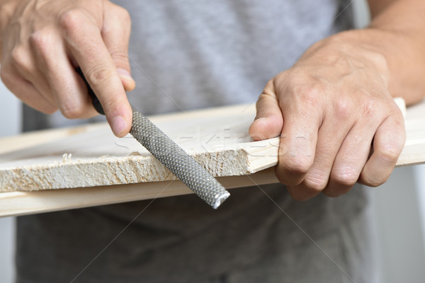 young man filing a wooden board with a rasp Stock photo © nito