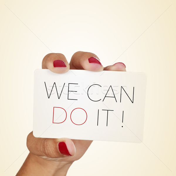 woman holds a signboard with the text we can do it Stock photo © nito
