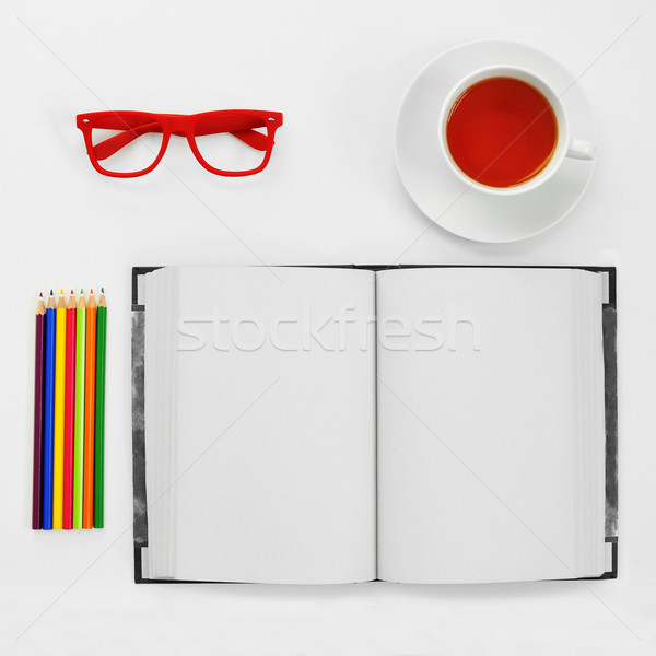 colored pencils, blank notebook, eyeglasses and cup of tea on a  Stock photo © nito