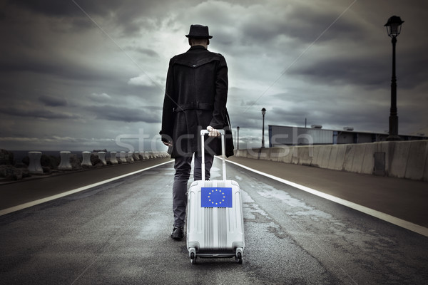 young man with a rolling suitcase with an European flag Stock photo © nito