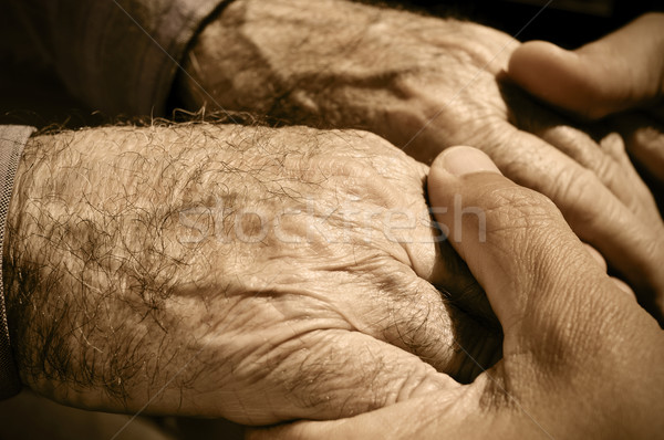 Stock photo: young man holding the hands of an old man