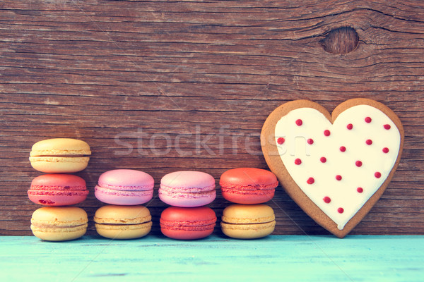 Stock photo: macarons and heart-shaped cookie on a blue rustic surface