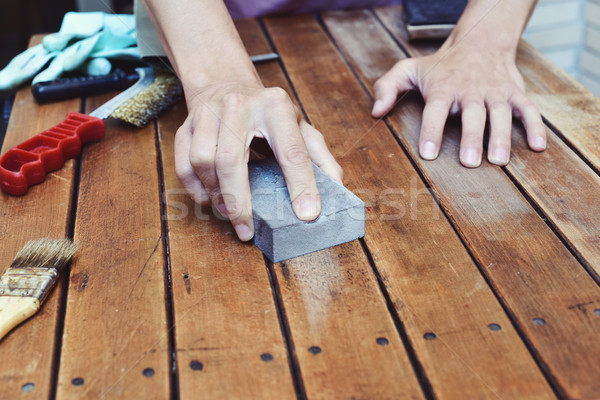 young man sanding a wooden table with a sanding block Stock photo © nito